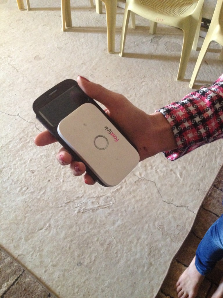 Reswan*, a young Syrian Kurdish woman from Qamishli, Syria, showing us her 'Fast Link' device and phone at a community center in Domiz refugee camp.